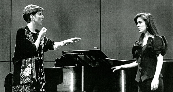woman teaching a voice student in front of piano
